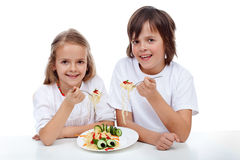 Happy kids eating pasta Royalty Free Stock Photos