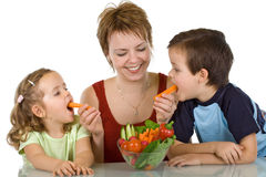 Happy kids eating vegetables Royalty Free Stock Photos