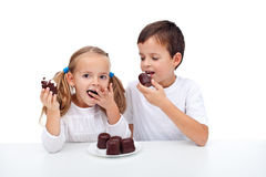 Happy kids eating whipped cream and chocolate dessert Stock Photo