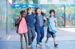 Happy kids embracing and smiling in the elementary schoolyard. I. Nterracial  friendship Royalty Free Stock Photos