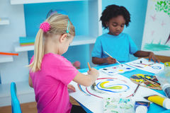 Happy kids enjoying arts and crafts painting. At their desk Royalty Free Stock Photo