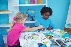 Happy kids enjoying arts and crafts painting Stock Photos