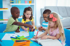 Happy kids enjoying arts and crafts together. In the bedroom stock image