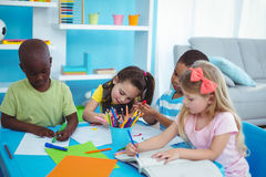 Happy kids enjoying arts and crafts together Stock Photos