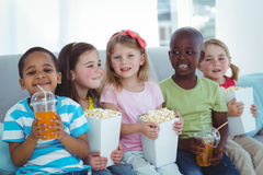 Happy kids enjoying popcorn and drinks while sitting Stock Images
