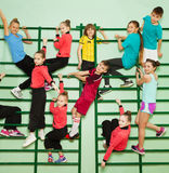 Happy kids exercising on wall-mounted gym ladder. Big group of happy preteen boys and girls in sweatsuits exercising on the bars of wall-mounted gym ladder Royalty Free Stock Photo