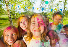 Happy kids' faces smeared with colored powder. Close-up portrait of happy kids, boys and girls, with faces smeared with colored powder stock images