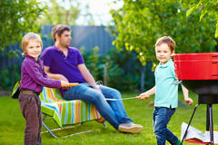 Happy kids fighting with kitchen items on picnic. Happy kids fighting playing with kitchen items on yard picnic Royalty Free Stock Photos