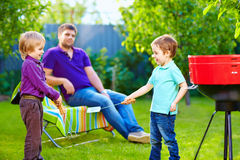 Happy kids fighting with kitchen items on picnic. Happy kids fighting playing with kitchen items on yard picnic Stock Image