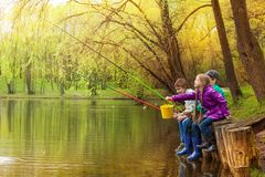 Happy kids fishing together near beautiful pond. Happy kids sitting and fishing together near the pond with colorful fishing poles in beautiful forest landscape Royalty Free Stock Image