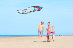 Happy kids flying kite on the beach stock images