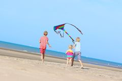 Happy kids flying kite on the beach Stock Photography