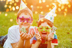 Happy kids friend in carnival party, lying on a green grass in s Royalty Free Stock Photo