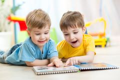 Happy kids friends reading together. Happy kids boys brothers reading together at home Royalty Free Stock Photo
