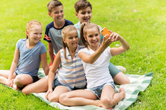 Happy kids or friends taking selfie in summer park. Friendship, childhood, technology and people concept - group of happy kids or friends taking selfie by Stock Photography