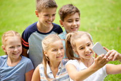 Happy kids or friends taking selfie in summer park. Friendship, childhood, technology and people concept - group of happy kids or friends taking selfie by Stock Photo