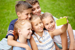Happy kids or friends taking selfie in summer park. Friendship, childhood, technology and people concept - group of happy kids or friends taking selfie by Stock Photos