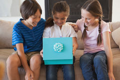 Happy kids with gift box in living room Royalty Free Stock Photos