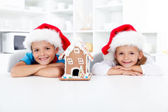 Happy kids with gingerbread house at christmas