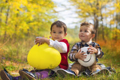 Happy kids girl and boy with balloons in autumn Royalty Free Stock Photo