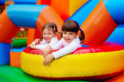 Happy kids, girls having fun on inflatable attraction playground Royalty Free Stock Photos