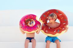 Happy kids in glasses and swimming trunks with donut rubber rings ready for summer vacation Royalty Free Stock Images