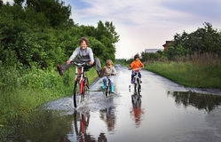 Happy kids are going through a puddle Stock Photos