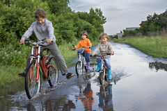 Happy kids are going through a puddle Stock Images