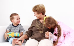 Happy kids with grandma Stock Images