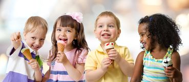 Happy kids group eating ice cream at a party in cafe. Four kids group eating ice cream at a party stock photo