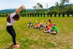 Happy kids guessing during charades game at summer camp. Happy kids sitting on a lawn quessing different animals shown by the girl leader, during charades game royalty free stock image