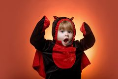 Happy kids on Halloween. Funny kids in carnival costumes on orange background. Scary face. Horror faces. Funny face. Children in america celebrate halloween stock photography