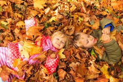 Happy kids having fun in autumn fall leaves Stock Photos