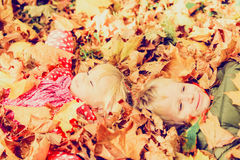Happy kids having fun in autumn fall leaves Royalty Free Stock Image