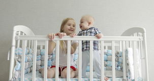 Happy kids having fun in a baby cot. 4K Happy kids having fun in a baby cot. Beautiful blonde girl blowing to the face of the little kid. Brother and sister stock video