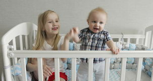 Happy kids having fun in a baby cot. 4K Happy kids having fun in a baby cot. Sister claps hands and sings to her younger brother stock video footage