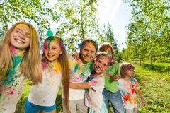 Happy kids having fun during color festival. Happy kids having fun smeared with colored powder during color festival, outdoor in summer stock image