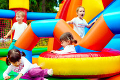 Happy kids, having fun on inflatable attraction playground Stock Photos