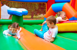 Happy kids having fun on inflatable attraction playground Stock Images