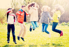 Happy kids having fun and jumping up. Happy smiling kids having fun and jumping up in spring field Royalty Free Stock Photos