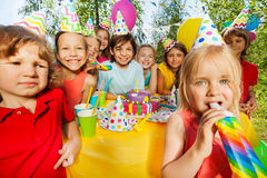 Happy kids having fun with party whistles Stock Photos