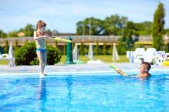 Happy kids having fun, playing in water park. Pool Stock Image