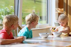Happy kids having healthy breakfast in the kitchen Royalty Free Stock Photography