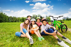 Happy kids in helmets sit on grass and smile Stock Images