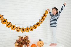 Happy kids help family to hang up decoration. Happy kids help her family to hang up the Halloween decoration to celebrate the holidays at living room royalty free stock photography