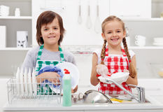 Happy kids helping in the kitchen royalty free stock photos