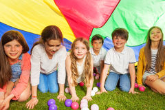 Happy kids hiding under colorful parachute outdoor Royalty Free Stock Photos