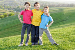 Happy kids on the hillside. Group of happy kids standing on the green grass on the hillside Stock Image