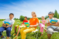 Happy kids hold exercise books and sit on chairs Stock Images