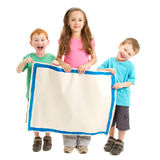 Happy kids holding blank painted sign. Three happy kids holding blank painted sign. Isolated on white Stock Image